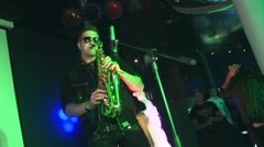 Saxophonist in sunglasses perform on stage of nightclub. Not real flame. Mic Stock Footage