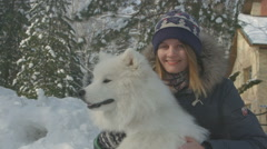 Cheerful girl pats and hugs beautiful white dog, samoyed - stock footage