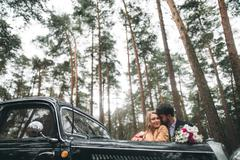 Gorgeous newlywed bride and groom posing in pine forest near retro car - stock photo