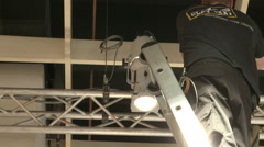 Worker setting up spotlights on the roof Stock Footage