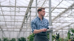 Florist holding accounting of plants in greenhouse - stock footage