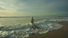 Man hit by rush of wave on beach Stock Footage