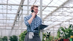 Young man talking on the phone in greenhouse. Stock Footage