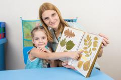 Five-year girl considering the herbarium of the leaves in the album with adul - stock photo