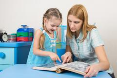 Adult young beautiful girl shows a five-year girl in the photo album sitting  Stock Photos