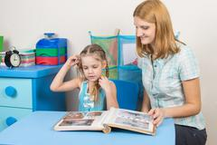 Mom shows her five-year-daughter photo album Stock Photos