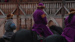 Male and female envoys on horseback staying in front of old medieval castle Stock Footage