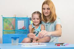 Mentor and five year old girl draws paints picture at the table in kindergart - stock photo