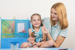 Mentor and five year old girl having fun looking at the brush to draw - stock photo