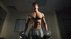 Strong man, bodybuilder exercising with dumbbells in a gym Stock Footage