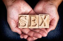 "Word ""Sex"" spelled out with wooden letters in woman hands - stock photo"