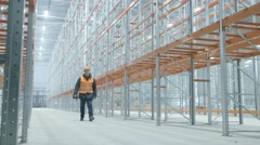 Worker comes in bright and modern warehouse Stock Footage