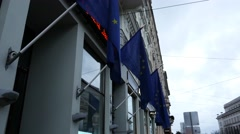 EU flags in front of builing with ticker Stock Footage