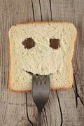 Happy toast with a fork in her mouth on a wooden - stock photo