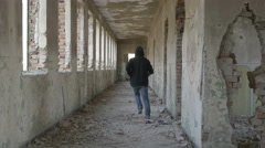 Hooded frightened young man running in an abandoned military building - stock footage