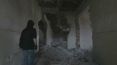 Hooded young man walking through the hallway of an abandoned building - stock footage