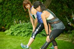 Two mature women keeping fit and streching before jogging Stock Photos
