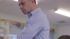 4K Teacher watching over young students working in school classroom - stock footage