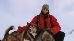 Man pets Siberian husky dogs during sled excursion in Longyearbyen, Norway. Stock Footage