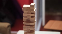 People playing Jenga in the cheerful company. - stock footage