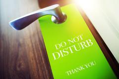 Do Not Disturb Green Paper Hotel Door Hanger. - stock photo