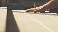 The young master hand touches the wooden boards in the sun. RAW video record Stock Footage