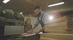 Industrial carpenter worker operating wood folding machine during wooden door Stock Footage
