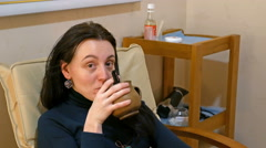 Smiley woman relaxes in armchair with cup of tea Stock Footage