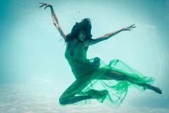 Brunette in evening gown swimming in pool underwater Stock Photos