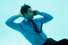 Businessman on the phone underwater in swimming pool Stock Photos