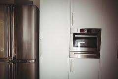 Fridge and oven in stylish kitchen at home Stock Photos