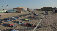 A Group of People Are lying And Relaxing During Yoga class on the shore. Stock Footage