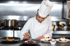 Chef putting finishing touch on dessert in a commercial kitchen Stock Photos
