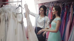consultant wedding salon helps to choose a dress for the bridesmaids - stock footage