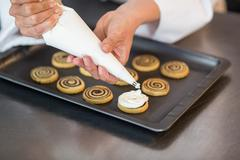 Chef piping icing on biscuits in a commercial kitchen Stock Photos