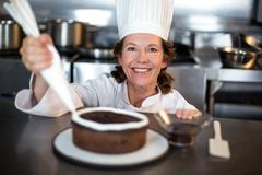 Chef piping icing on cake in a commercial kitchen Stock Photos