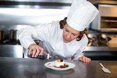 Chef pouring sauce over a dessert in a commercial kitchen Stock Photos
