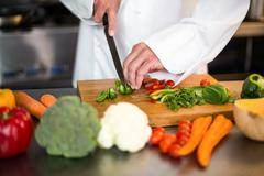 Chef slicing vegetables on wooden board in a commercial kitchen Stock Photos
