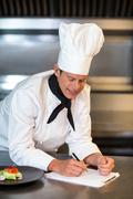 Chef planning his menu in a commercial kitchen Stock Photos