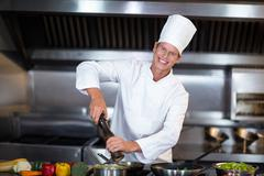 Happy chef seasoning his dish in a commercial kitchen Stock Photos