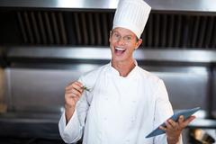 Happy chef using tablet pc while cooking in a commercial kitchen Stock Photos