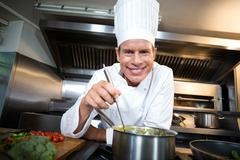 Happy chef smiling at camera in a commercial kitchen Stock Photos