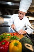 Chef preparing vegetables at counter in a commercial kitchen Stock Photos