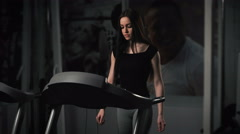 Attractive young woman doing cardio exercise on treadmill at gym Stock Footage