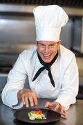 Happy chef showing his dish in a commercial kitchen Stock Photos