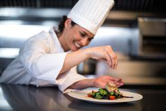 Happy chef seasoning her dish in a commercial kitchen Stock Photos