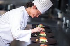 Happy chef with her dishes in a commercial kitchen Stock Photos