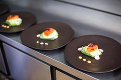 Elegant dishes on counter in a commercial kitchen Stock Photos