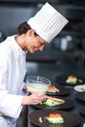 Happy chef finishing her dishes in a commercial kitchen Stock Photos