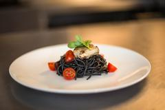 Squid ink spaghetti dish with basil in a commercial kitchen Stock Photos